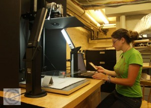 Small image showing Lisa Duncan performing photo documentation on artworks.