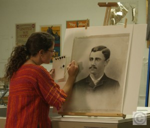 Small image showing Lisa Duncan conserving an artwork on an easel in a conservation lab