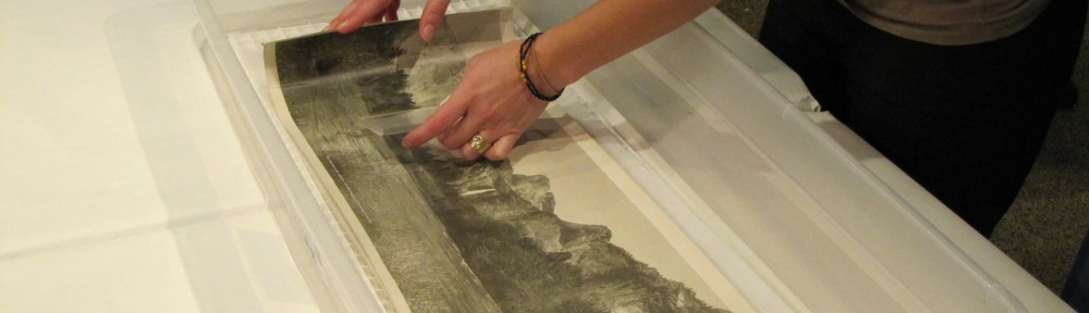 Image showing Lisa Duncan's hands performing a wet treatment on a long narrow artwork on paper in a plastic basin