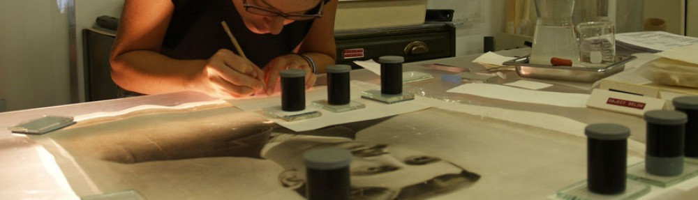 Image of Lisa Duncan performing art conservation treatments on an artwork showing a man's head and shoulders. On the artwork, several treatments are weighted under small stacks of blotter paper, plexiglass and weights.