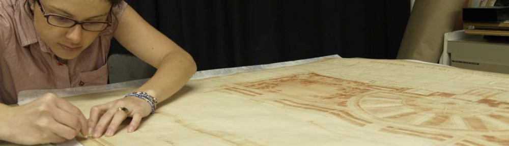 Image showing Lisa Duncan performing a conservation treatment of a large work on paper.